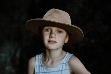 Moody image of young boy wearing hat in dark cave in tropical north Queensland