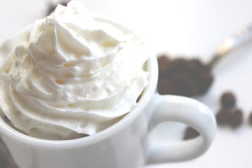 Closeup photo of espresso with whipped cream. In the background grains of coffee