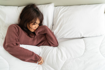 Asian woman sleeping on bed in morning