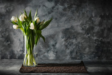 Wall Mural - Dark mood background and fresh flowers of tulips.