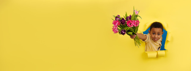 Smiling African-American with a bouquet of Tulip flowers looks out of torn paper gives flowers on yellow background. Concept of Valentine's Day, mother's Day, eighth of March, spring