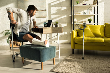 Side view of man with broken leg looking at laptop on table in living room