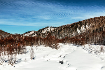Beautiful winter landscape with a frozen river and forest-covered mountains on a Sunny winter day