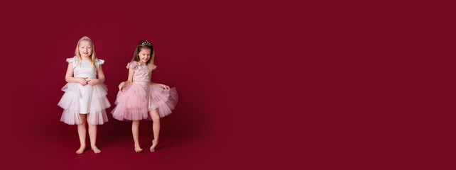 Beautiful little girls princess playing in luxury pink, white and silver dresses isolated on red background. Funny face, different emotions Wall mural