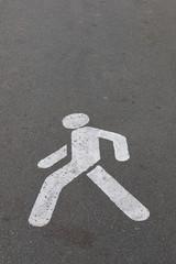 white pedestrian figure, painted on asphalt