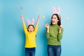 Portrait of nice attractive lovely glad cheerful cheery girls mom mum holding in hands eggs sticks having fun isolated over bright vivid shine vibrant blue color background