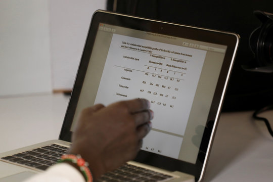 PhD student Collins Kipkorir Kebeni points to data comparing human and rhino antibiotics resistance on a computer at the Zoology lab of the Maseno University