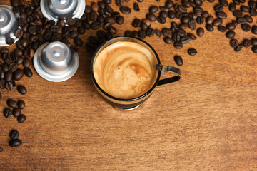 Cup of coffee with capsules and coffee beans