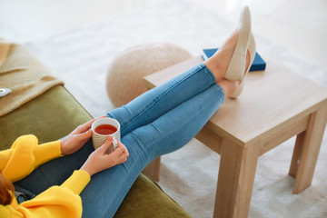 Young woman with cup of tea resting at home