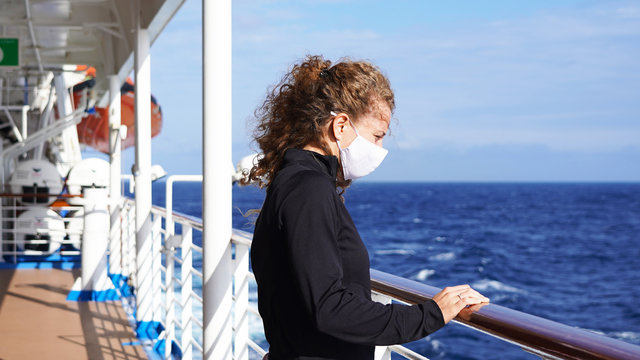 Curly girl in a medical respirator on board a cruise ship on a sunny day against the background of the sea. quarantined european girl cruise ship