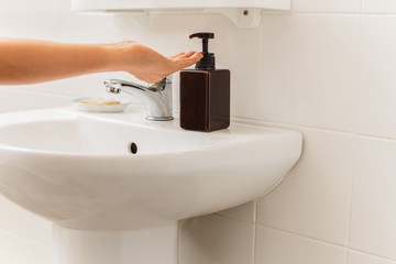 Hand with liquid soap from bottle in bathroom Healthcare concept.