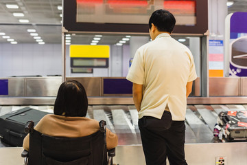 Caretaker with woman in wheelchair waiting for luggage on conveyor belt.