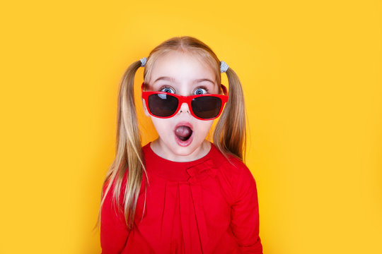 Shocked little girl in red sunglasses over yellow background