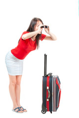Before planting. A young brautiful woman in a red blouse and white skirt, looking through binoculars and holding a small travel suitcase, on a white background, isolated.