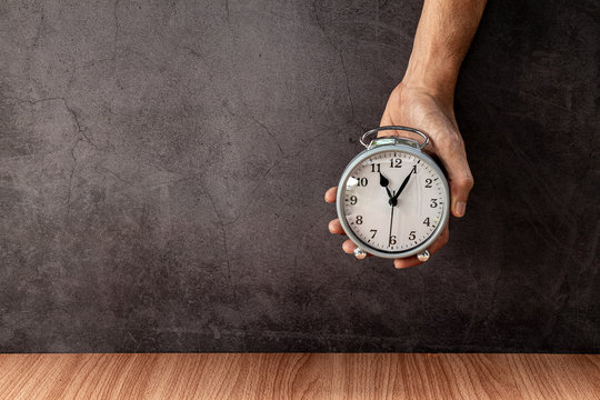 A man holding alarm clock on old gray concrete wall for background.