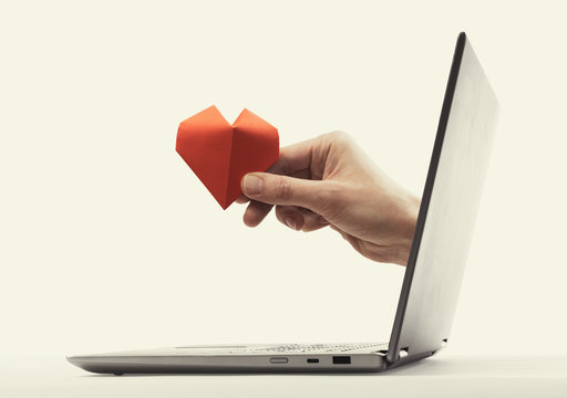The woman hand with red paper heart stick out of a laptop screen. Concept of gift giving, donation, insurance and dating.