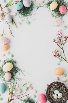 Top down view of an Easter border flat lay including robin's eggs, chocolate eggs and nests in desaturated colours.