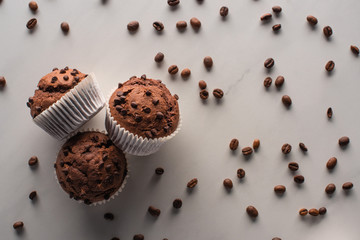 top view of fresh chocolate muffins with coffee beans on marble surface