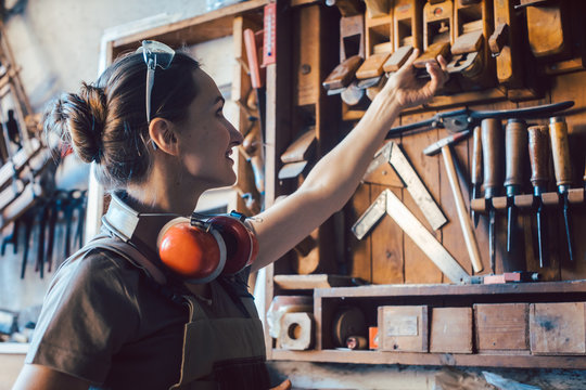 Woman carpenter choosing a tool to work on wood