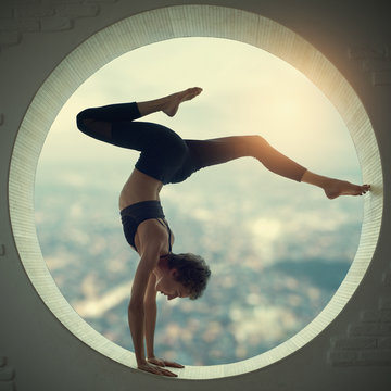 Beautiful sporty fit yogi woman practices yoga handstand asana Bhuja Vrischikasana - Scorpion handstand pose in a window