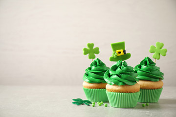 Delicious decorated cupcakes on light table, space for text. St. Patrick's Day celebration