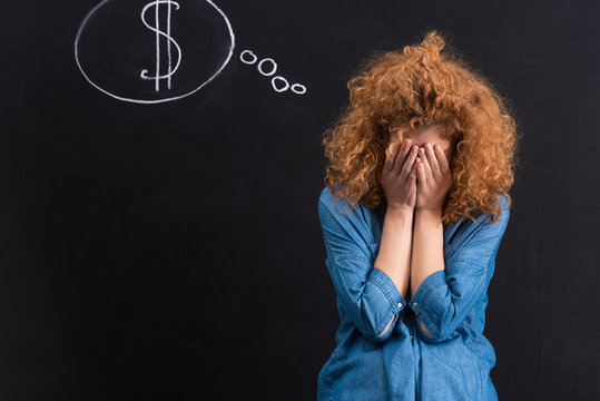 frustrated girl with dollar sign in thought bubble on chalkboard
