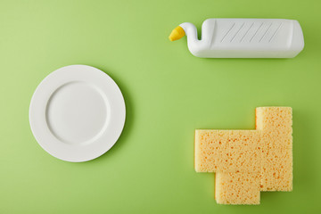top view of plate, sponges and bottle for dish washing on green