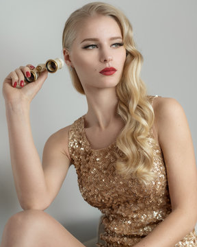 Woman in golden dress portrait holds theatrical binoculars. Hollywood style hair, red lipstick, 1950s years rich stale. Perfect skin for beauty salon or party.