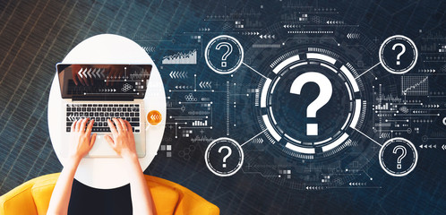 Wall Mural - Question marks with person using a laptop on a white table