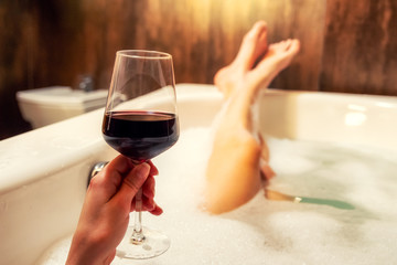Tuinposter Wijn Relaxing in bathtub with glass of red wine
