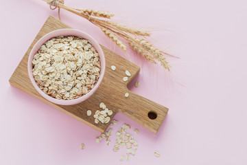 Bowl of dry oat flakes with ears of wheat on light background