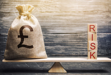 Money bag and wooden blocks with the word Risk on the scales. Business risk management and assessment. Strategic, financial and operational risks. Insurance. Economics and finance. Brexit