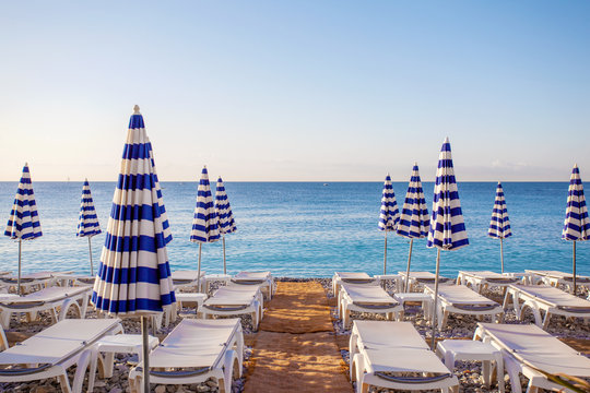 View of the blue striped umbrellas on the beach in Nice, Cote d'Azur, Southern France