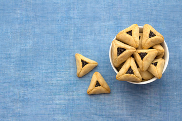 Traditional sweets for Jewish holiday of Purim. Hamantashen cookies or Aman ears, triangular cookies with poppy seeds on blue background, top view, free space
