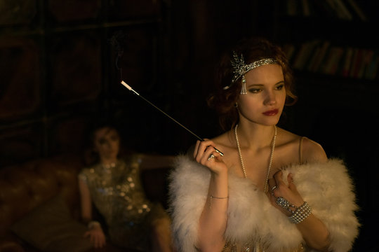 Two beautiful female models dressed in vintage 1920s style fashion posing in dark moody room. Roaring twenties concept. Women couple relations concept.