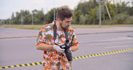 Man photographer walking behind the crime tape taking pictures of car accident in the street. Portrait of severe handsome police man looking around providing an investigation.