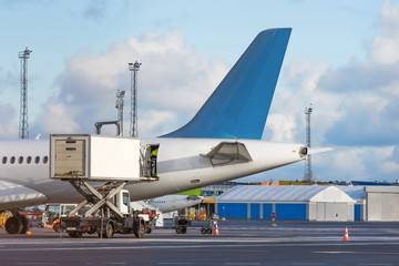 Airplane tail view- service before flights, service machine for loading.