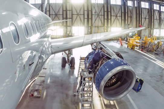 A working mechanic is repairing a passenger plane engine in a hangar.