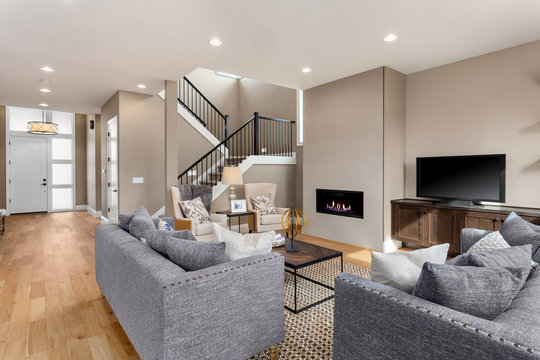 Beautiful living room interior in new home. Features fireplace with fire, built in shelving and cabinets, hardwood floors, and open concept design.