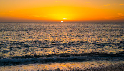 sunset over the sea, typical beautiful sunset on the beach by the ocean, vacation summer landscape with high contrast