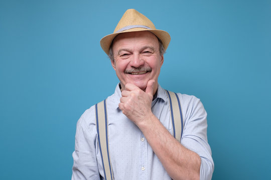 Portrait of friendly confident senior man in summer hat standing isolated over blue background. Positivre facial human emotion.