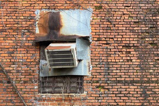 a rusty old air conditioner on a vintage red brick wall