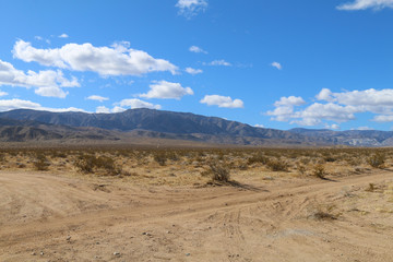 a dry desert road with mountains and blue sky