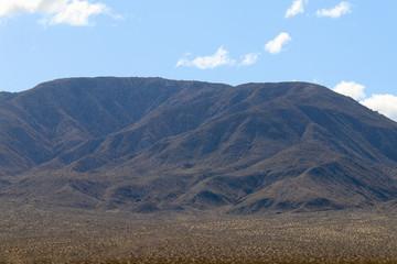 a distant desert mountain range on a cloudy blue sky
