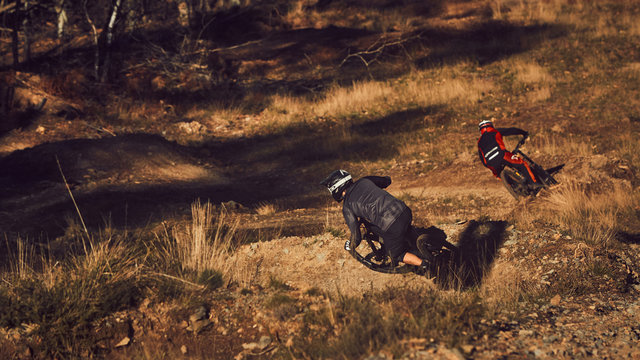 two mountain bike riders go round turns