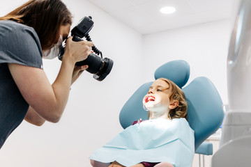 Dentist taking picture of girl receiving dental treatment