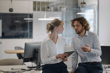 Businessman and businesswoman with tablet talking in office