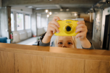 Boy taking a picture with a camera in office