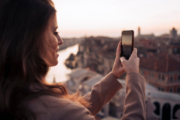 Young couple taking cell phone pictures on a balcony above the city of Venice, Italy
