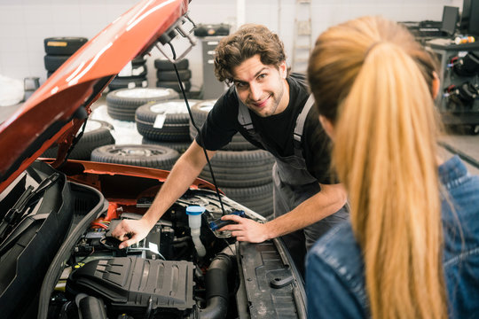 Car mechanic looking at client in workshop